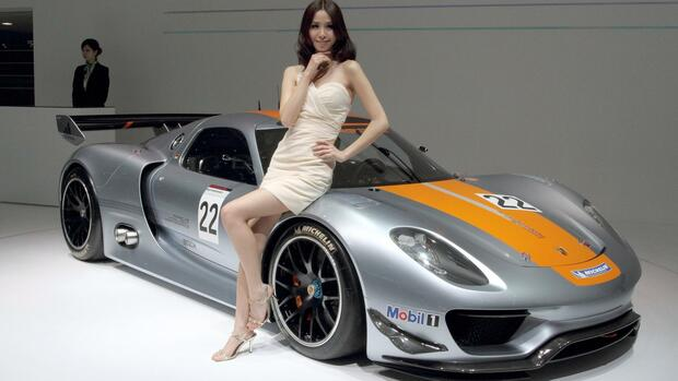 A model stands next to a Porsche RSR 918 sports car at the 14th Auto Shanghai Motor Show Quelle: dpa