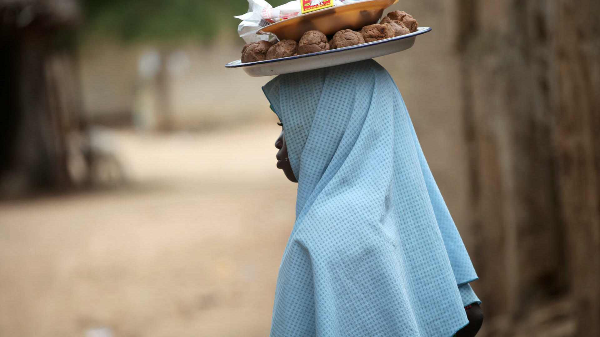 A girl hawks local snacks in the Dal neighbourhood before the break of fast on the second day of the holy month of Ramadan in Nigeria Quelle: REUTERS
