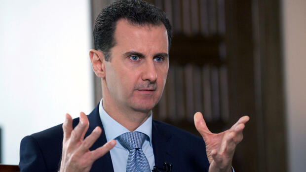 A handout picture released by the official Syrian Arab News Agency (SANA) on March 30, 2016 shows President Bashar al-Assad speaking to a journalist during an interview with Russia's RIA Novosti state news agency in the Syrian capital Damascus. In the interview, Assad named Saudi Arabia, Turkey, France and Britain as countries that are