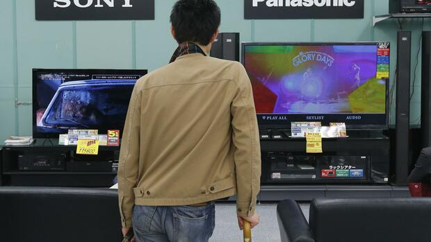 A man looks at Sony and Panasonic TV sets at an electronics shop in Tokyo Quelle: REUTERS
