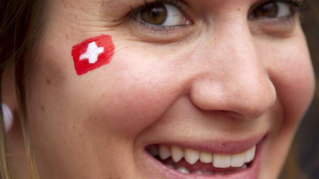 A woman has a painted Swiss flag on her face Quelle: Reuters