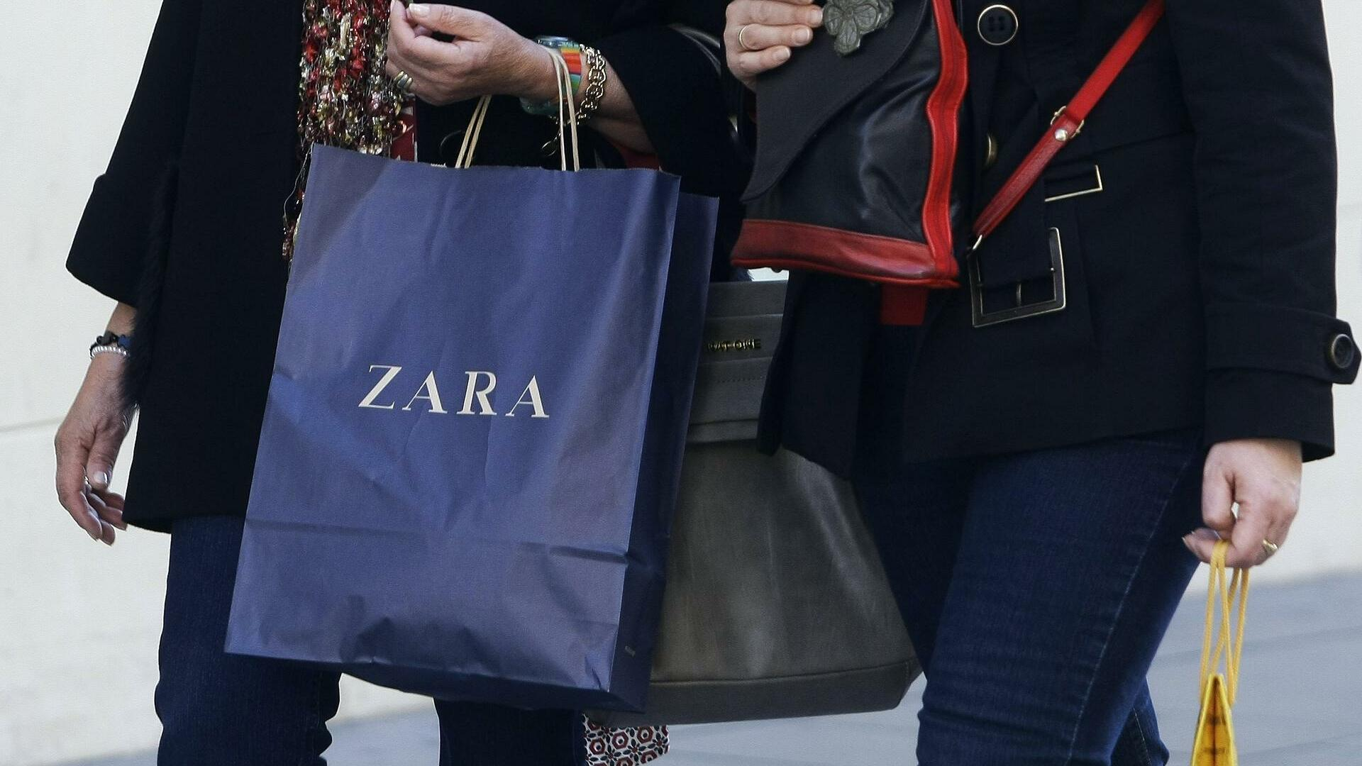 A woman holds a Zara shopping bag in Madrid Quelle: REUTERS
