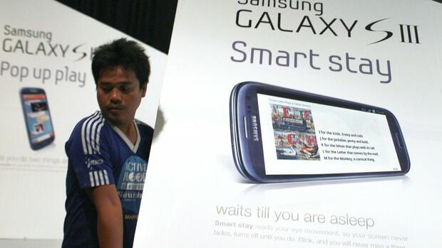 A worker moves an advertisement for the Samsung Galaxy SIII smartphone Quelle: REUTERS