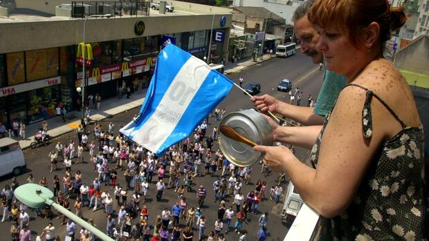 huGO-BildID: 2117341 Juan Carlos Aramburu, 55, and his wife Liliana Cane, 44, wave an Argentine flag and bang a pan from their balcony, as protesters who feel their money is locked in the financial system demonstrate below, in a commercial area where a couple bank branches are located, on the outskirts of Buenos Aires, Argentina Wednesday, Jan. 16, 2002.(AP Photo/Daniel Luna) Quelle: AP