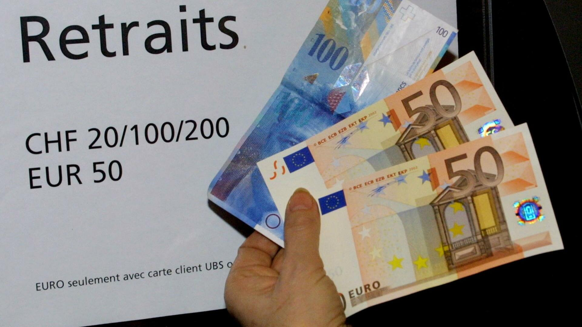 A woman holds 100 euro (pink banknotes at bottom) and 100 Swiss francs (blue banknote at top) she withdrew from an ATM in a bank in Geneva Quelle: AP
