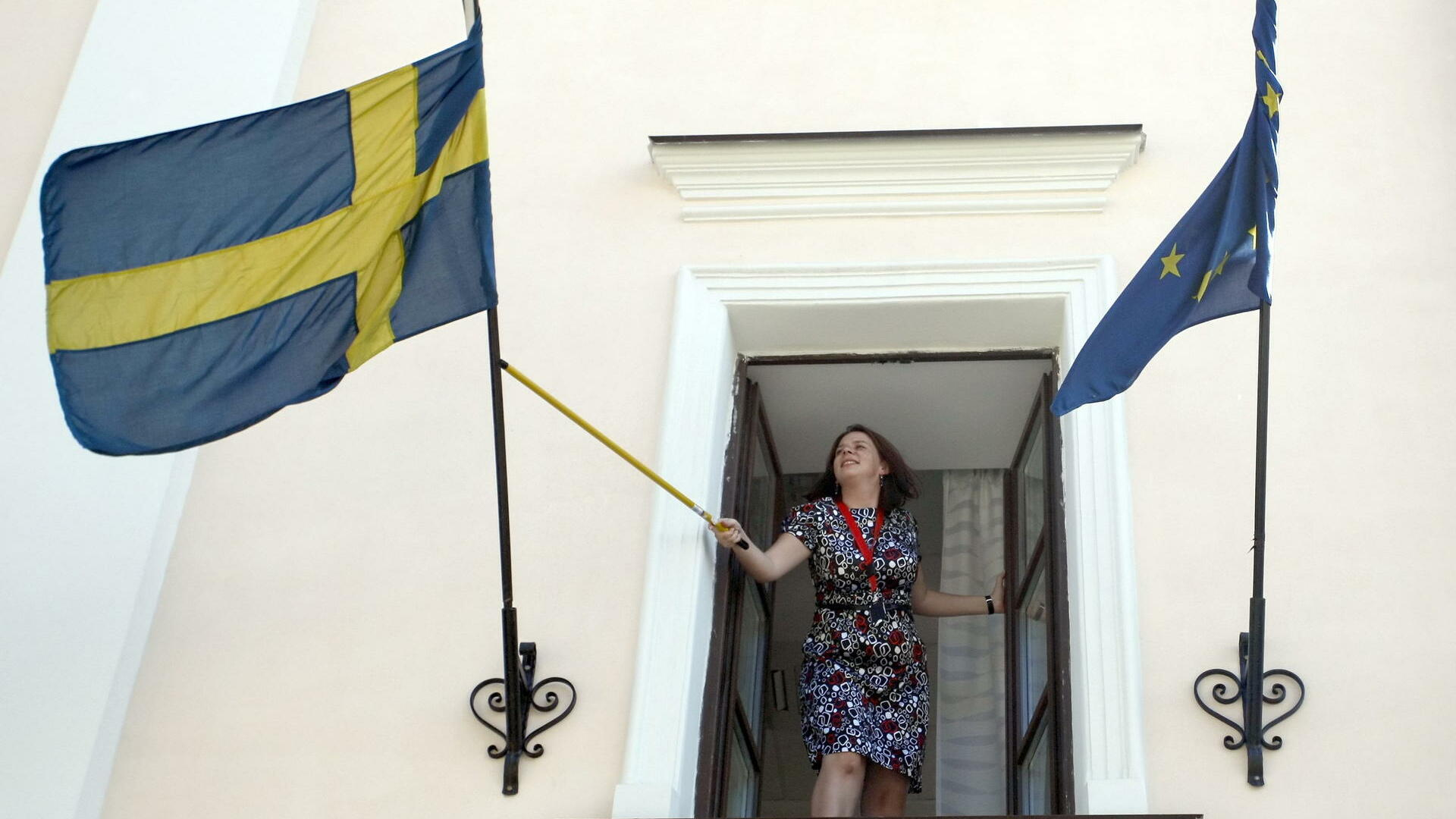 An Swedish embassy employee adjusts a Swedish Quelle: dpa