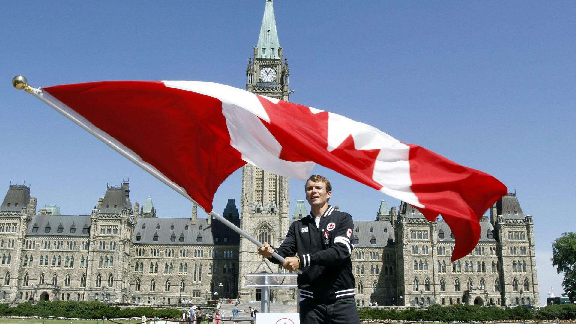 Triathlete Simon Whitfield of British Columbia, waves the Canadian Flag on Parliament Hill in Ottawa. Quelle: dapd