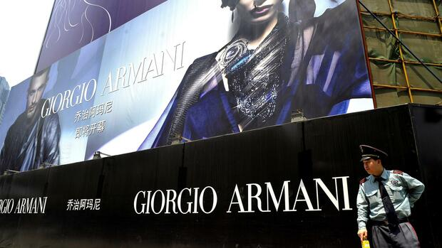 A security guard stands beside a billboard of luxury goods brand Giorgio Armani where the firms store will open Quelle: dpa