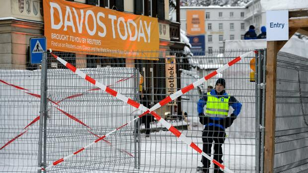 A Swiss police officer surveys the area during the World Economic Forum (WEF) annual meeting in Davos, on January 20, 2016. A string of jihadist attacks and rising risks to the global economy overshadow the opening of the annual gathering of the world's rich and powerful in a snow-blanketed Swiss ski resort. Even as heads of state, billionaires and Hollywood megastar Leonardo DiCaprio were arriving, the International Monetary Fund (IMF) sounded the alarm on January 19, 2016 about perils in the major emerging market economies and lowered its outlook for global economic growth this year. / AFP / FABRICE COFFRINI Quelle: AFP