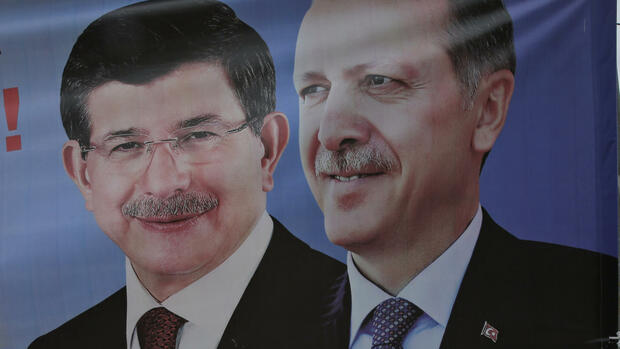 FILE - In this May 28, 2015, file photo, a man walks past a poster with pictures of Turkish Prime Minister and leader of the AKP party Ahmet Davutoglu, left, and Turkey's president, Recep Tayyip Erdogan, also the party's former leader, in Istanbul. Erdogan had harsh words Friday May 6, 2016 for Europe, saying his nation won't reform its anti-terrorism legislation just for the sake of getting visa-free travel for its citizens there. The tough talk comes at a time when moderate Davutoglu has stepped down, a move that Erdogan's critics fear will help the president further consolidate his power. (AP Photo/Lefteris Pitarakis, File) Quelle: AP