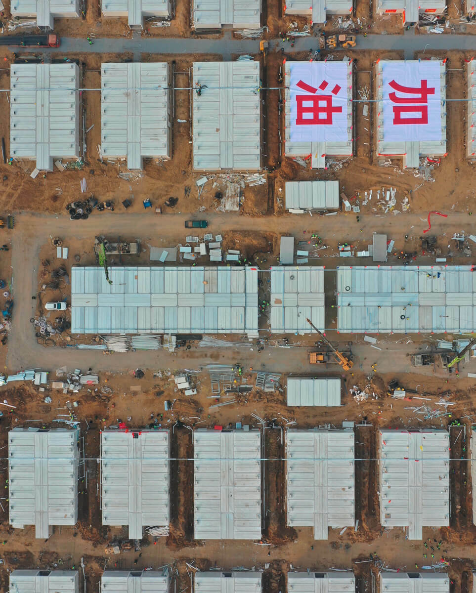 """Auf dem Dach zweier Container steht auf Chinesich """"gib Gas!"""". Ein Slogan, mit dem sich Chinesen anfeuern und Mut zusprechen."""