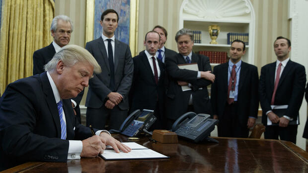 President Donald Trump signs an executive order implementing a federal government hiring freeze, Monday, Jan. 23, 2017, in the Oval Office of the White House in Washington. (AP Photo/Evan Vucci) Quelle: AP
