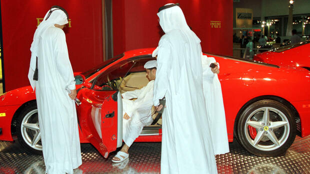 Men in Arab traditional dress check the new 2000 model of Ferrari 360 Modena priced at about $140,000 Quelle: AP