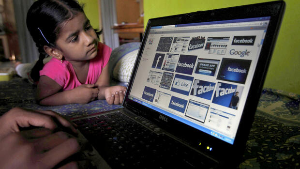 a child looks at a laptop displaying Facebook logos Quelle: dapd