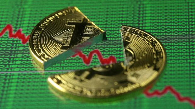 FILE PHOTO: Broken representation of the Bitcoin virtual currency, placed on a monitor that displays stock graph and binary codes, are seen in this illustration picture, December 21, 2017. REUTERS/Dado Ruvic/Illustration/File Photo Quelle: REUTERS