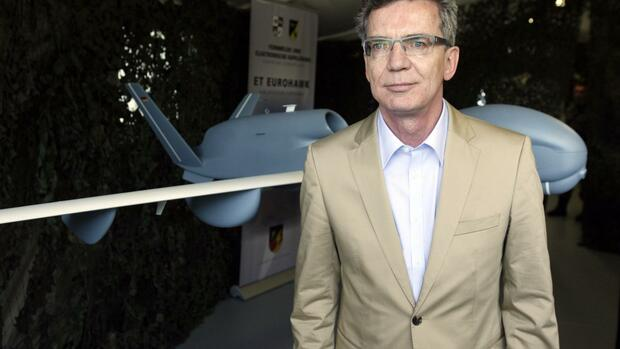 German Defence Minister Thomas de Maiziere stands in front of a model of the EuroHawk unmanned aerial vehicle (UAV) Quelle: REUTERS