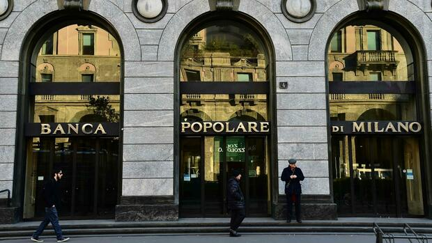 "(FILES) This file photo taken on January 19, 2016 shows People walking past an office of the Italian bank ""Banca Popolare di Milano"" in Milan. Banco Popolare and BPM shareholders are set to vote on October 15, 2016 on a proposed merger to create the country's third-largest lender, a much-anticipated accord expected to consolidate Italy's troubled banking sector. / AFP PHOTO / GIUSEPPE CACACE Quelle: AFP"