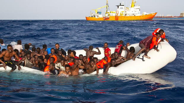 "(FILE) epa05265406 A handout photgraph made available by the Ong Sos Méditerranée showing migrants on a sinking inflatable boat before being rescued by the Aquarius ship of the humanitarian group SOS Mediterranee, and taken to Lampedusa, Italy, 18 April 2016. Six bodies were recovered and 108 migrants were rescued from a semi-submerged rubber dinghy as boat arrivals accelerate amid calm seas. A private rescue ship, the Aquarius, run by humanitarian group SOS Mediterranee found the bodies on the rubber dingy on 17 April 2016. EPA/ONG SOS MEDITERRANEE / HANDOUT HANDOUT EDITORIAL USE ONLY/NO SALES (zu ""UNHCR bestätigt neue Flüchtlingstragödie - 500 Tote befürchtet"") +++(c) dpa - Bildfunk+++ Quelle: dpa"