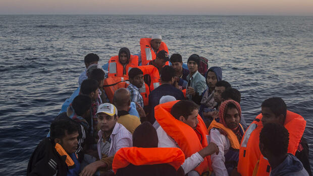 Refugees and migrants overcrowd a wooden boat during a rescue operation on the Mediterranean sea, about 19 miles north of Az Zawiyah, Libya, on Thursday, July 21, 2016. Over the past weeks, vessels from NGOs, several nations' military fleets and passing cargo ships have all rescued migrants from unseaworthy boats launched from Libya's shores. (AP Photo/Santi Palacios) Quelle: AP
