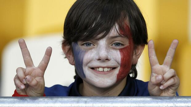 A young France's fan with the face painted in national flag colors shows victory sign as he waits for the start of the Group D Euro 2012 soccer match against Sweden Quelle: REUTERS