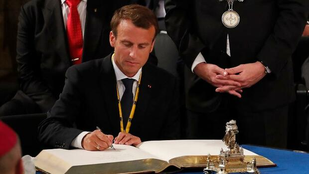 French President Emmanuel Macron signs a book after being awarded the Charlemagne Prize during a ceremony in Aachen, Germany May 10, 2018. REUTERS/Wolfgang Rattay Quelle: Reuters