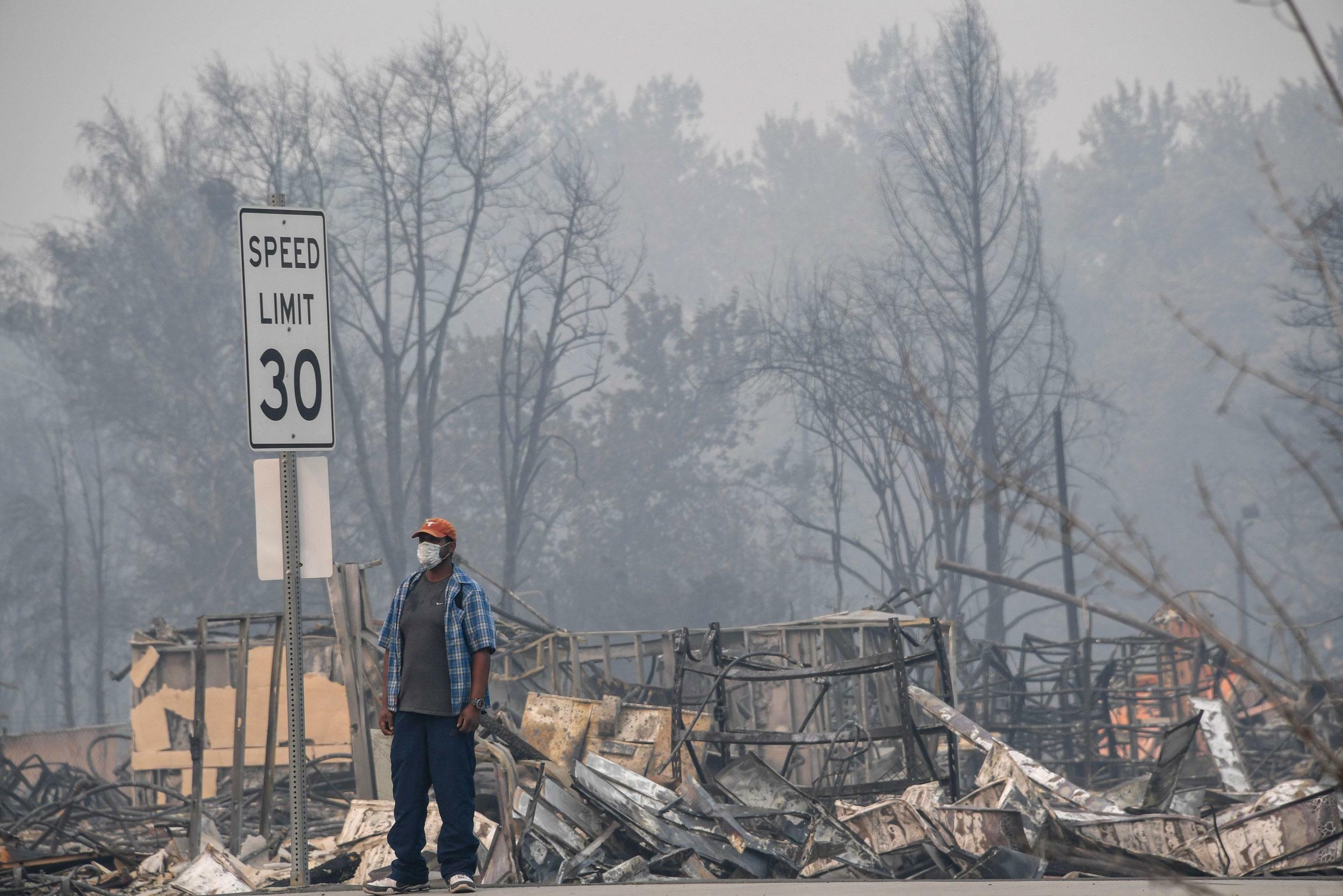 Ein Mann steht vor einer verbrannten Landschaft