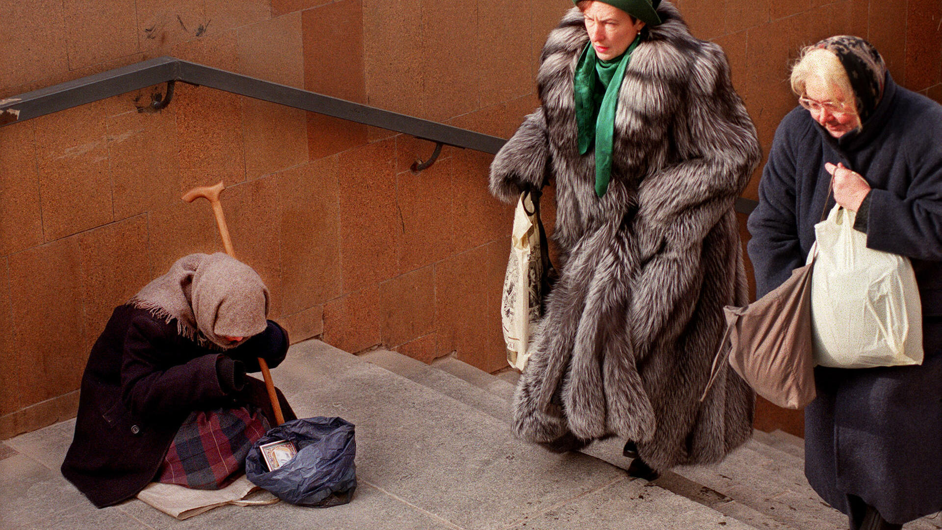 Two women walk past a beggar sitting on the steps of an underground pedestrian crossing in downtown Moscow, Quelle: AP