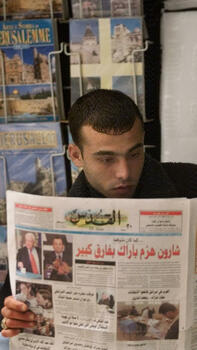 An Arab man reads an Arabic newspaper featuring front page pictures and the story of Ariel Sharon's victory against Ehud Barak Quelle: AP