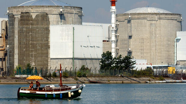 A small boat floats by the nuclear plant at Fessenheim Quelle: AP