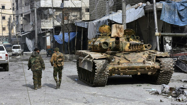 In this photo released by the Syrian official news agency SANA, two Syrian soldiers pass by a tank where government forces have captured wide areas in eastern Aleppo, Syria, Monday, Dec. 12, 2016. Syria's military said Monday it has regained control of 98 percent of eastern Aleppo, as government forces close in the last remaining sliver of a rebel enclave packed with fighters as well as tens of thousands of civilians. (SANA via AP) Quelle: AP