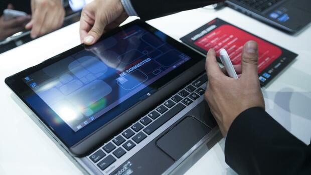 A man opens a Toshiba Satellite U920 tablet notebook at the IFA consumer electronics fair in Berlin, Quelle: REUTERS