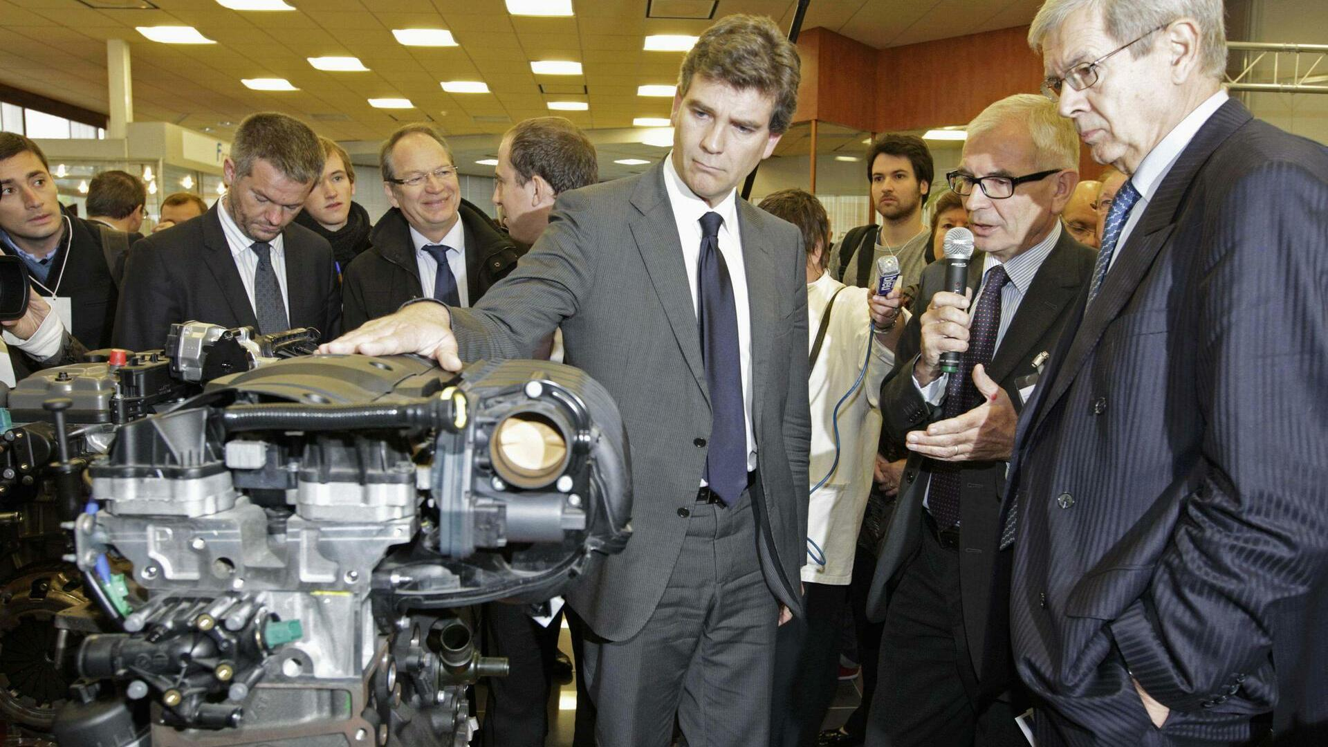 Minister for Industrial Recovery Arnaud Montebourg (C) and Chief Executive of French carmaker PSA Peugeot Citroen Philippe Varin (R), visit