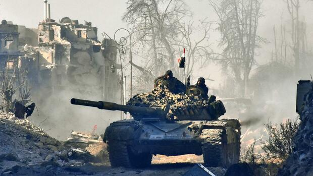 TOPSHOT - Syrian pro-government forces manoeuver a tank in the newly retaken area of Sahat al-Melh and Qasr al-Adly in Aleppo's Old City on December 8, 2016. President Bashar al-Assad said victory for his forces in Aleppo would be a