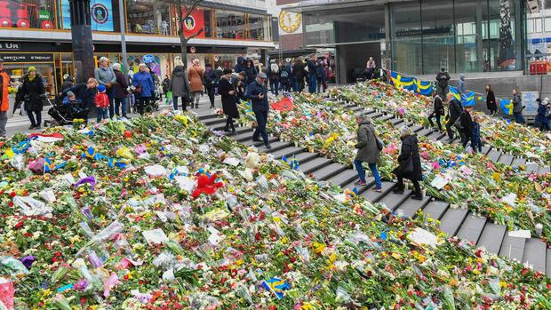 People walk by flowers near Ahlens department store at the pedestrian street Drottninggatan in central Stockholm on April 12, 2017, five days after a hijacked beer truck plowed into pedestrians there killing four people, injuring 15 others. / AFP PHOTO / TT News Agency / Federik SANDBERG / Sweden OUT Quelle: AFP