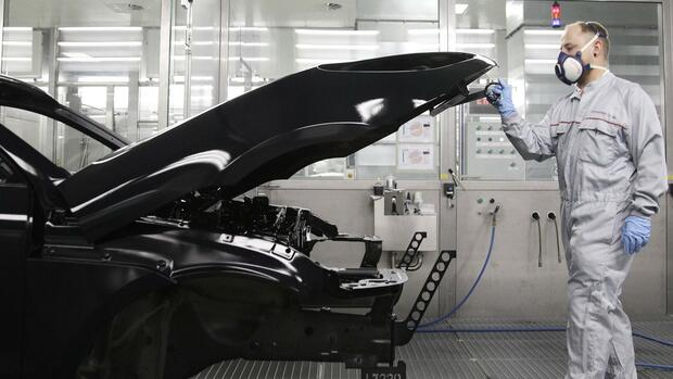 A worker opens the engine hood of a Porsche Macan at the new plant in the eastern German city of Leipzig February 11, 2014. Porsche's Leipzig production plant, which produces the German luxury carmaker's Macan series, was officially opened on February 11. REUTERS/Tobias Schwarz (GERMANY - Tags: BUSINESS) Quelle: Reuters