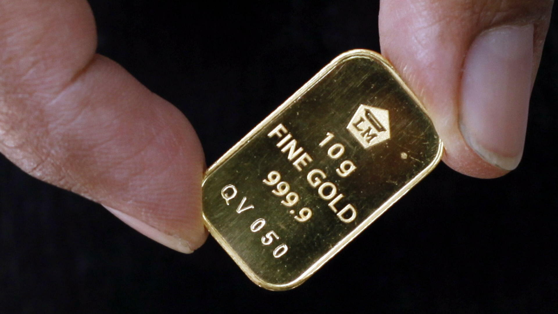 An Indonesian customer holds a 10 grams fine gold Quelle: dpa