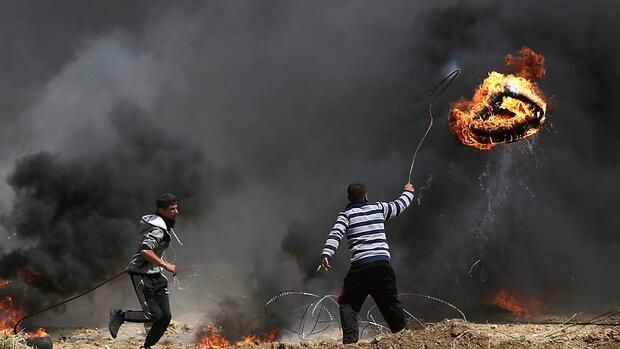 Palästinensische Demonstranten werfen einenbrennenden Reifen inRichtung israelischerSoldaten. Quelle dpa