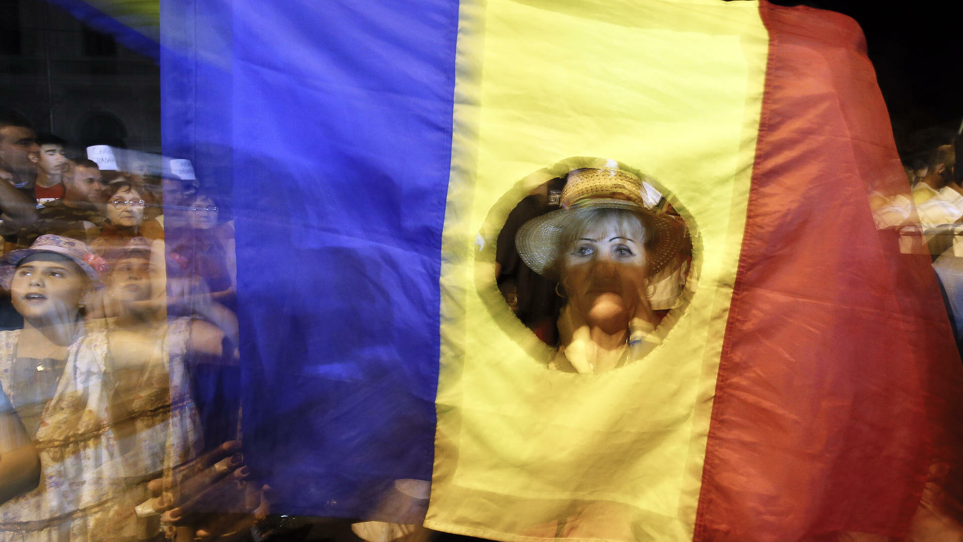 A woman peers through a Romanian flag during a protest against President Traian Basescu in Bucharest, Romania, Quelle: dapd