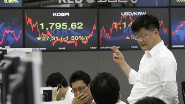 Currency traders talk in front of the screens showing the Korea Composite Stock Price Index Quelle: dapd