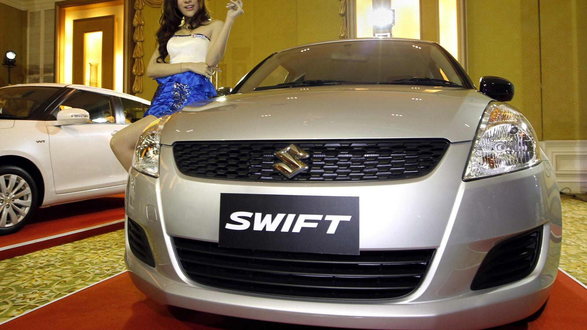A Thai model pose with the new eco-car Suzuki Swift during a press conference Quelle: dpa