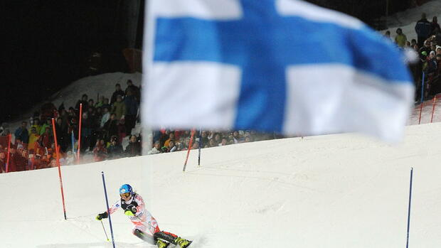 A Finnish flag flies in the wind as Tanja Poutiainen of Finland skies towards Quelle: dpa