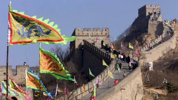 Visitors tour a section of the Great Wall at Badaling north of Beijing, which has been decorated with dragon flags Quelle: REUTERS