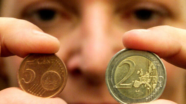 Frauke Theis from Schleswig checks the new Euro currency,5-Eurocent coin, left, and the 2-Euro coin, right Quelle: AP