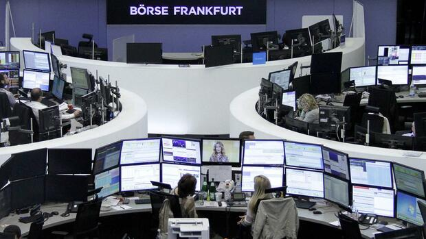Traders work at their desks in front of the German share price index, DAX board, at the stock exchange in Frankfurt, Germany, May 12, 2016. REUTERS/Staff/Remote Quelle: Reuters