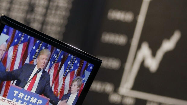 US President-elected Donald Trump is displayed on a television screen with the curve of the German stock index DAX in background at the stock market in Frankfurt, Germany, Wednesday, Nov. 9, 2016. The DAX started lower compared to the closing the day before. (AP Photo/Michael Probst) Quelle: AP