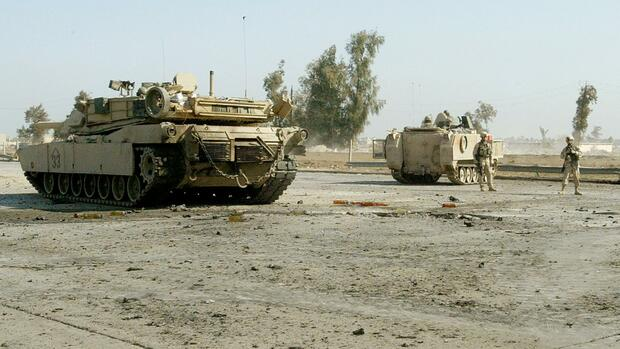 A U.S. tank and a Bradley fighting vehicle stand at the scene of a suicide car bomb attack on Baghdad's airport road Quelle: REUTERS