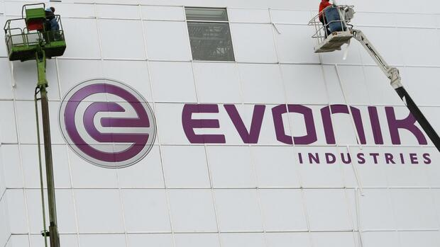 workers fixing a huge advertising banner of German company Evonik Quelle: REUTERS